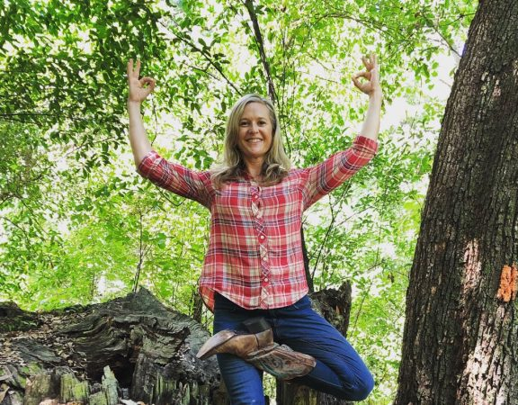 Blonde woman strikes yoga pose while standing on tree stump
