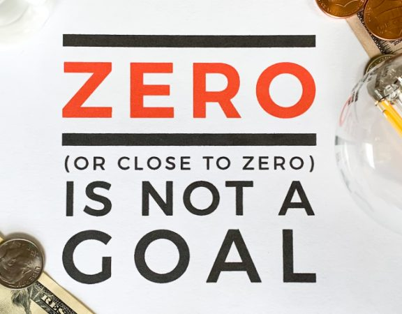 "Graphics over white table, money, lightbulb. ""Zero is not a goal"""